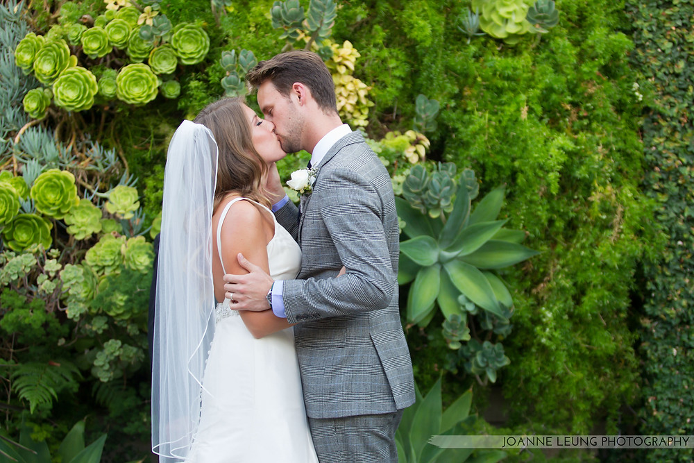 Succulent Wall Bride and Groom kissing at wedding