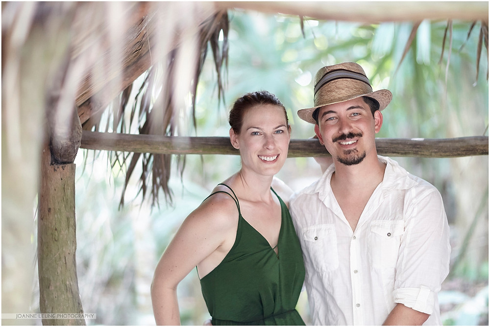 portrait of bride and groom at a straw hut in tulum