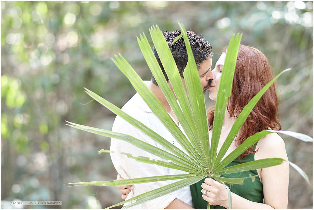couple kissing behind a leaf in tulum mexico