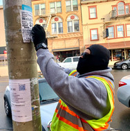 Graffiti abatement worker removes illegal postings from a Clement Street utility pole.