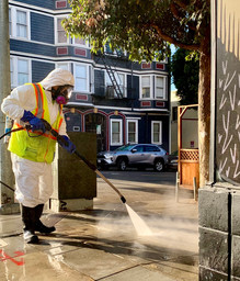 Tommy Lam power washes grime off the sidewalk.
