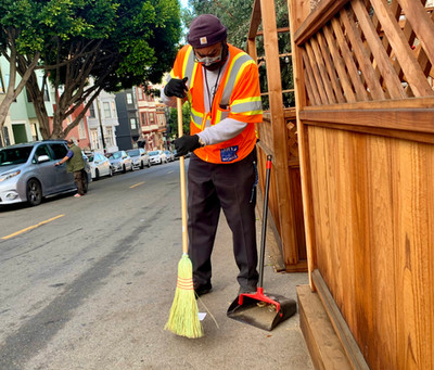 Mark Simmons sweeps up around a parklet in North Beach.