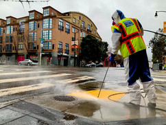 A street cleaner power washes grime off a Valencia Street sidewalk.