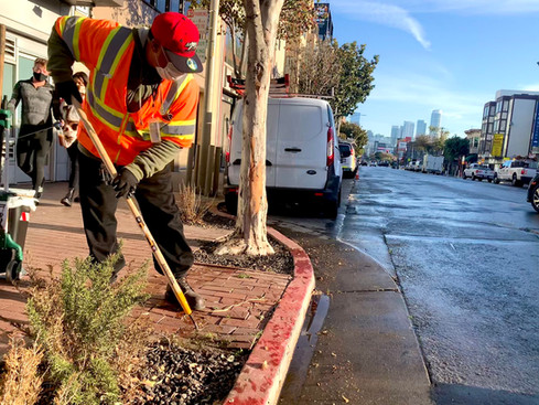 A street cleaner takes extra time to clear weeds during the CleanCorridorsSF operation.