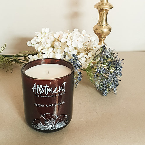 Soy candle in amber glass jar beside flowers