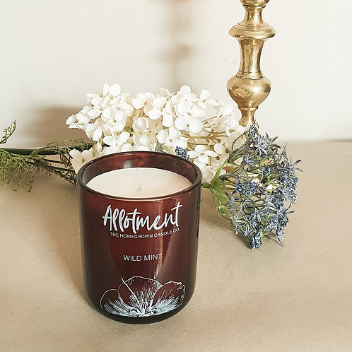 Luxury soy candle in amber glass jar beside flowers
