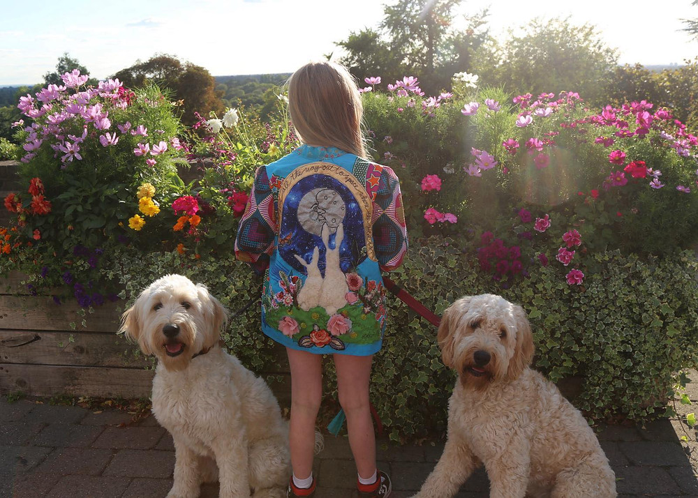 Girl stands between two white dogs wearing a kimono jacket with bunnies on
