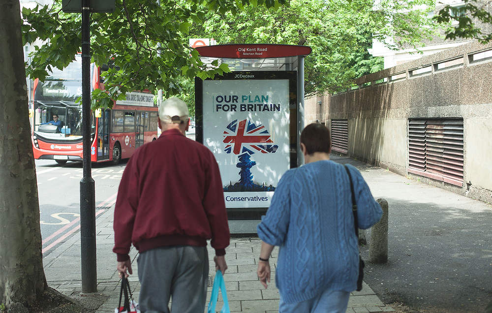 Two people walking towards an anti-Tory subvertising ad hacked bus stop poster. The poster is the Conservative party logo redone as a nuclear mushroom cloud