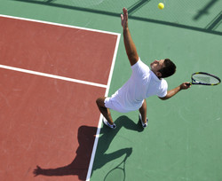 young man play tennis outdoor on orange