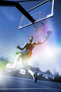 A basketball player drives to the hoop f