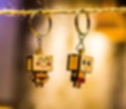 Two little keyring people with box head made out of wood with UV ink printed faces and swimmers hanging from a piece of string