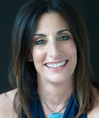 Headshot of Tapping/EFT Expert Julie Schiffman smiling in deep blue top and turquoise necklace