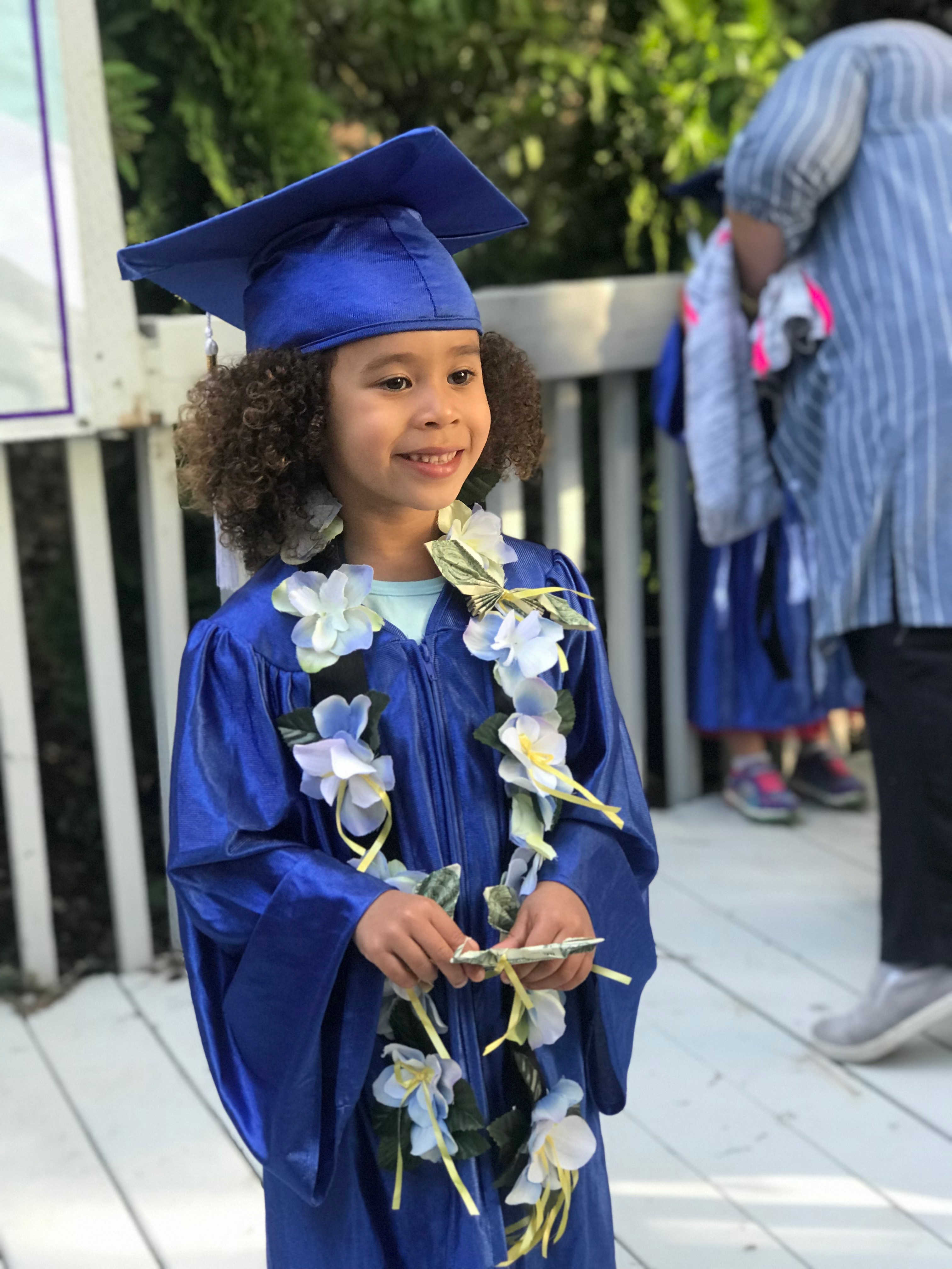 preschool graduate wearing a money lei
