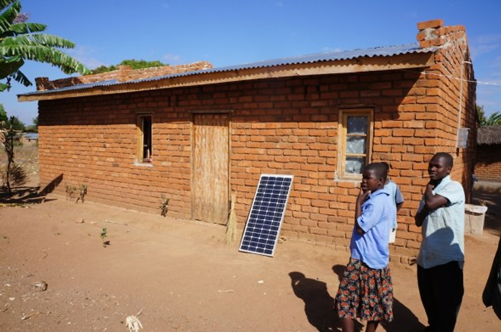 Completed brick house with a tin roof in Malawi! Kondwani started a business in photography and also selling vegetables. The family now has a solar panel and wiring for lights in his house. They are waiting for the electrification project to reach their neighborhood.