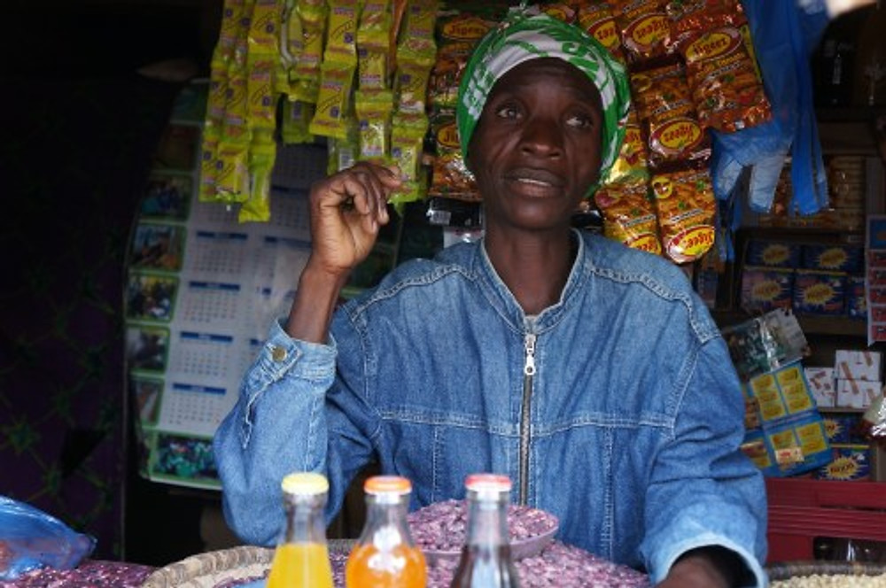 Love's Bean Shop is the only one in the market that sells dried beans, which are a popular source of protein. Love is HIV+ and uses some of her business profit to travel to the nearest town to receive the treatment that keeps her healthy.