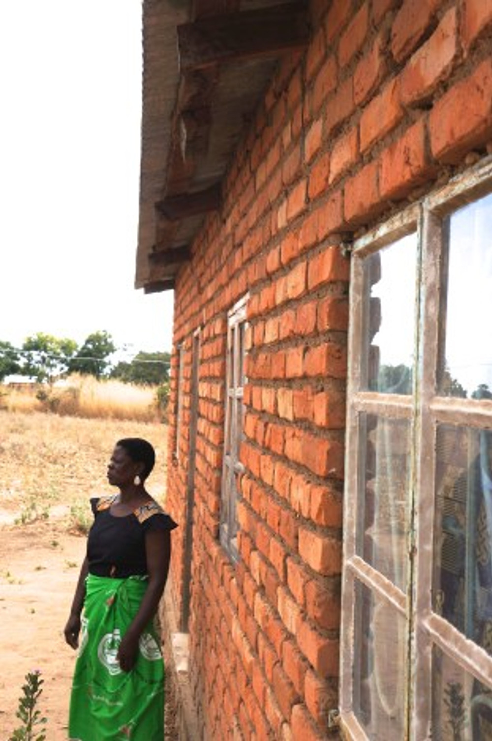 Harriet in front of the house she built with business profits and a low-interest loan and now rents out to a school teacher.