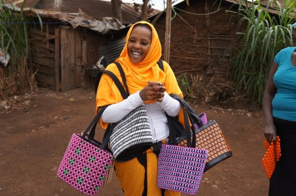 Habiba Sabuno showing off some of the beaded purses that are models for the training workshop.