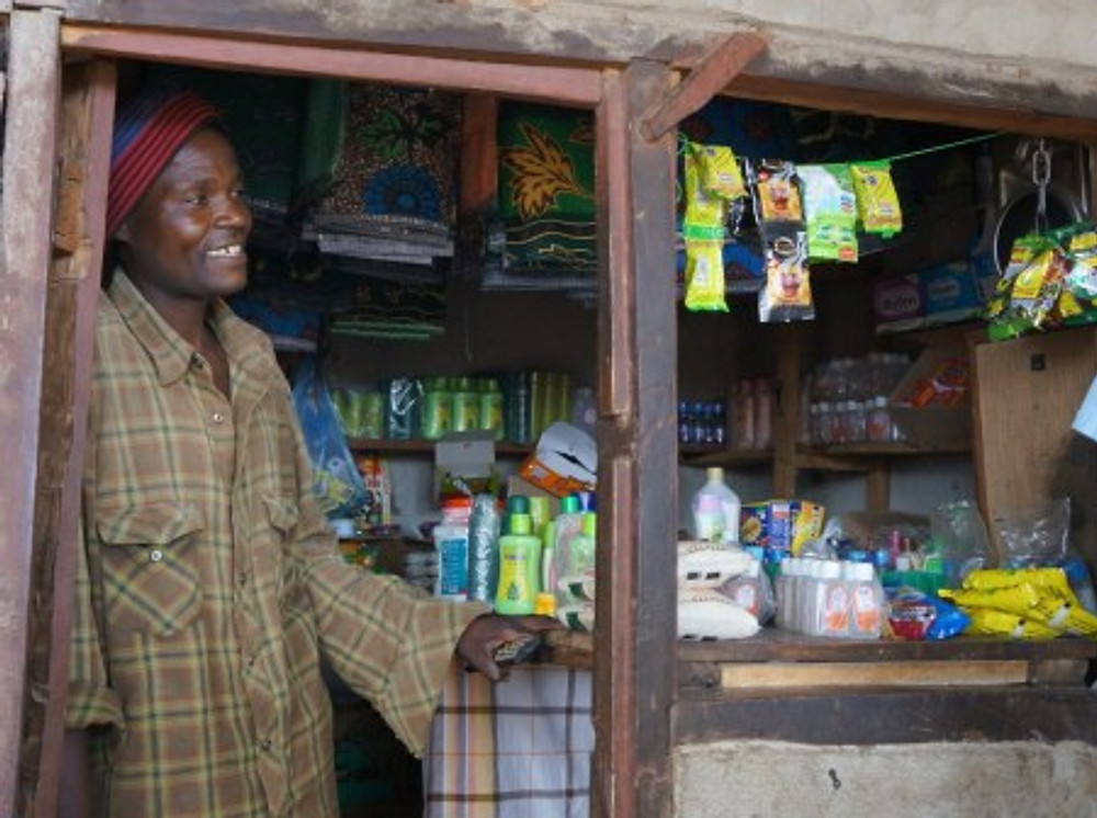 """Brown Ngoma is expanding his family's store, building a home, and now """"when his family is sick he can pay for a private hospital."""" (Manyamula, Malawi)"""