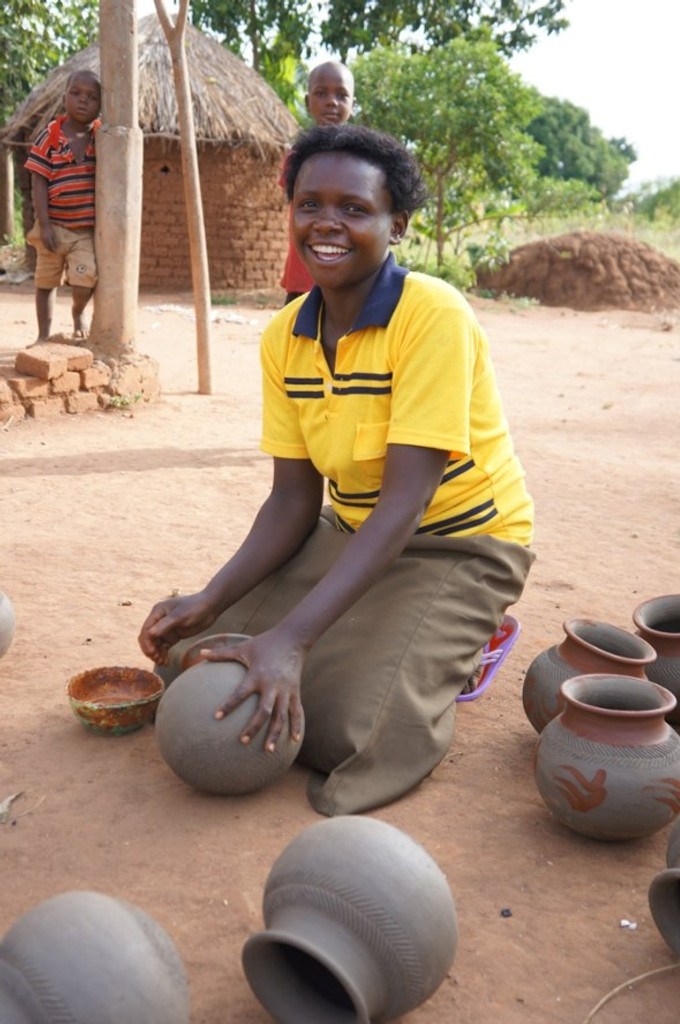 This woman and her husband started a pottery business in Uganda. He forms the pots and she fires and paints them.