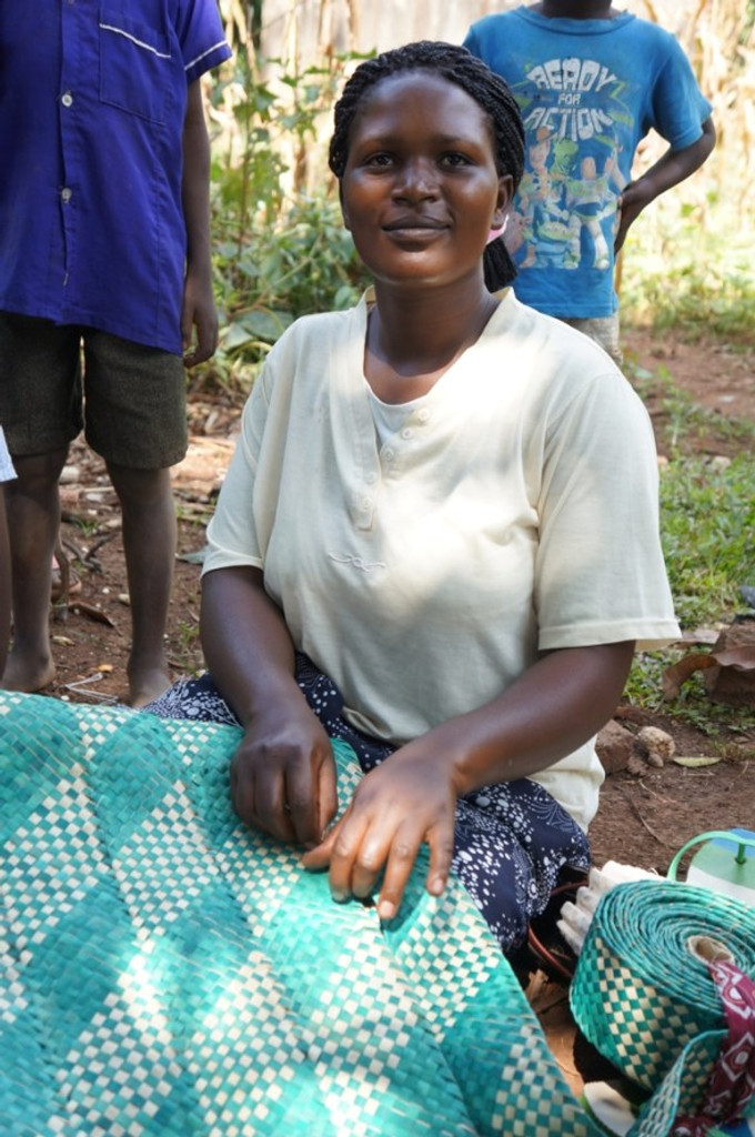 Ruth shows us one of the mats she's made to sell. Before the Small Business Fund grant the family was just subsistence farming, now their farm has grown so that they have enough to sell. (Uganda)