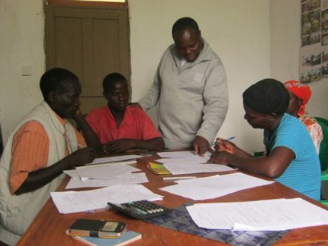 Stanly, Janet, and other new grant recipients completing their business plans with the guidance of Canaan Gondwe (standing).