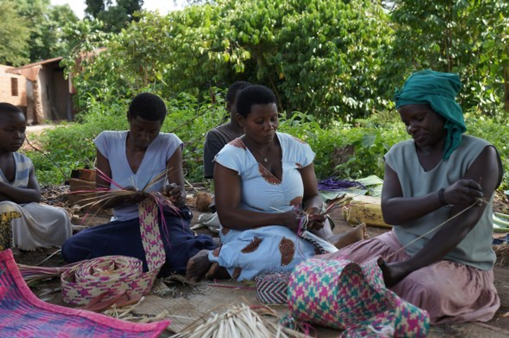 """This group of women meet twice a week to weave mats together under the trees. """"People laugh when you are going [to market with your mats], but not when you are returning [with money]."""""""