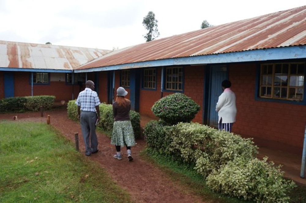 Samuel and Rhoda show Tanya the 6 classrooms that SIA built in 2002.