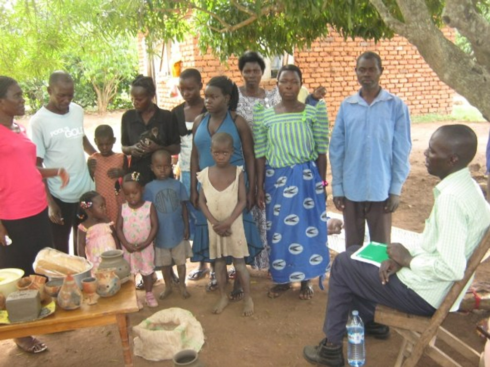 Yuba Robert and his extended family show us their pottery, including a clay savings box. They have been able to pay for school fees, build a house, and pay for another person to plow their fields. Godfrey Matovu, local SBF coordinator is seated on the right.