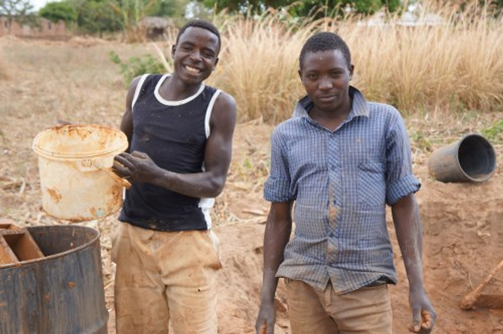 Rev. Issac has hired these two young men to form bricks for a new rental house. They will make about 15,000 bricks for the project, which will be left to dry for 3 days in the sun. The bricks will then be  burned to increase their strength. The men will earn about 1 cent per brick, or about $150 for the whole project.