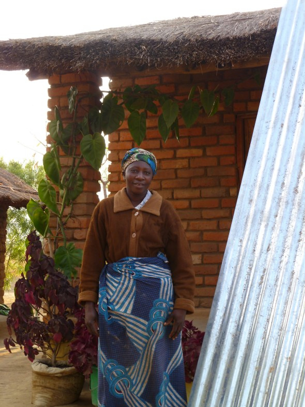 Steria in 2011. Using the profit from her donut business, she was buying iron roofing sheets one at a time. Her roof was thatched with grass at the time.