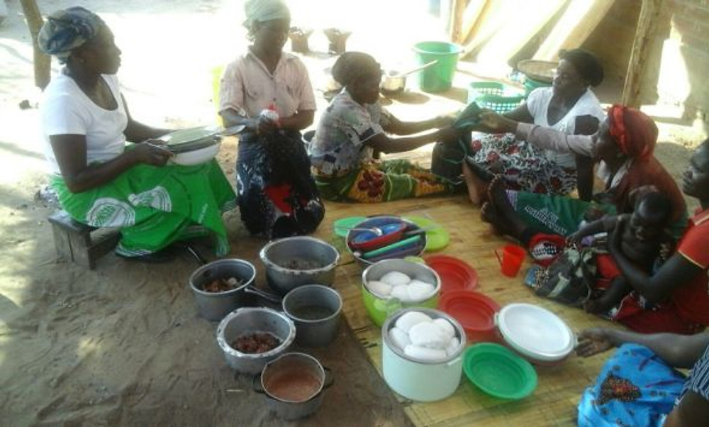 Women cooking together in Malawi. They are taking part of a Nutrition and Health workshop.