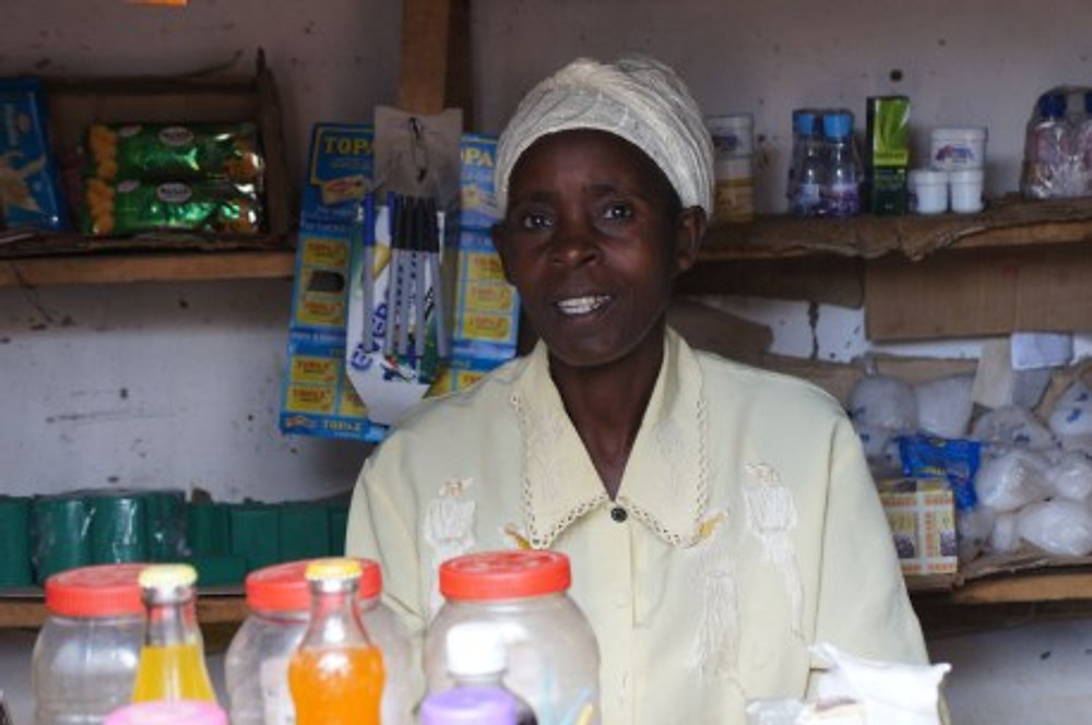 Rose is a member of the Manyamula COMSIP Cooperative and received a low-interest loan to open her shop. She is now eating and dressing better and she was able to buy a good bed.