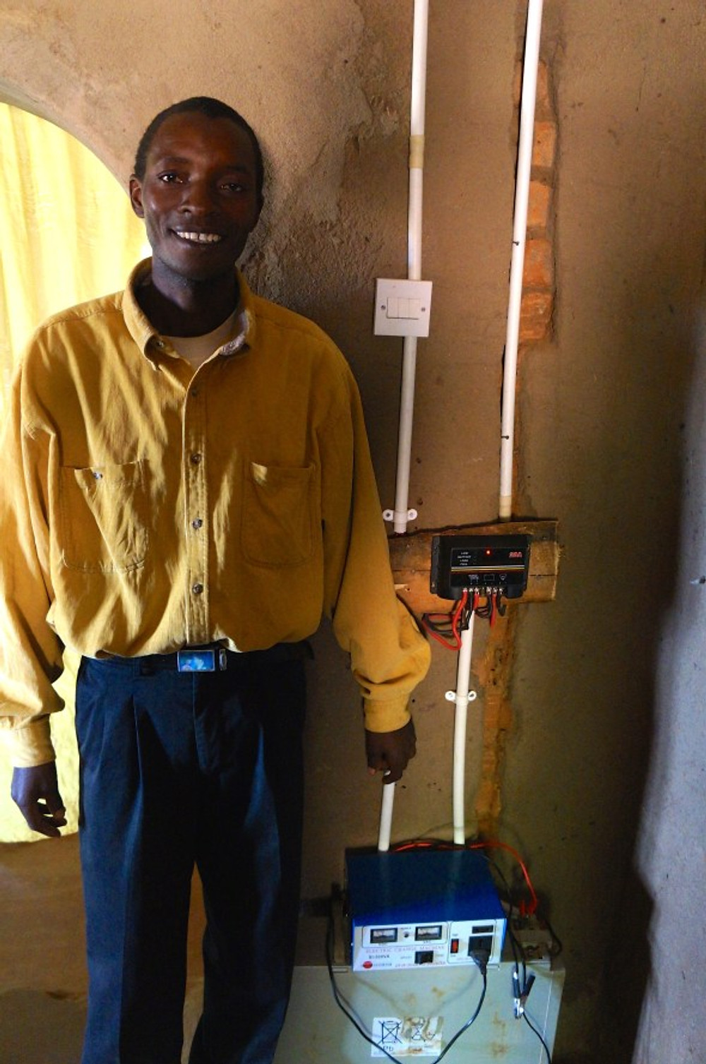 Mbwenu stands proudly next to his solar panel charging station. This battery is charged with the solar energy and can power the lights and appliances in the evening. He put together the system on his own.