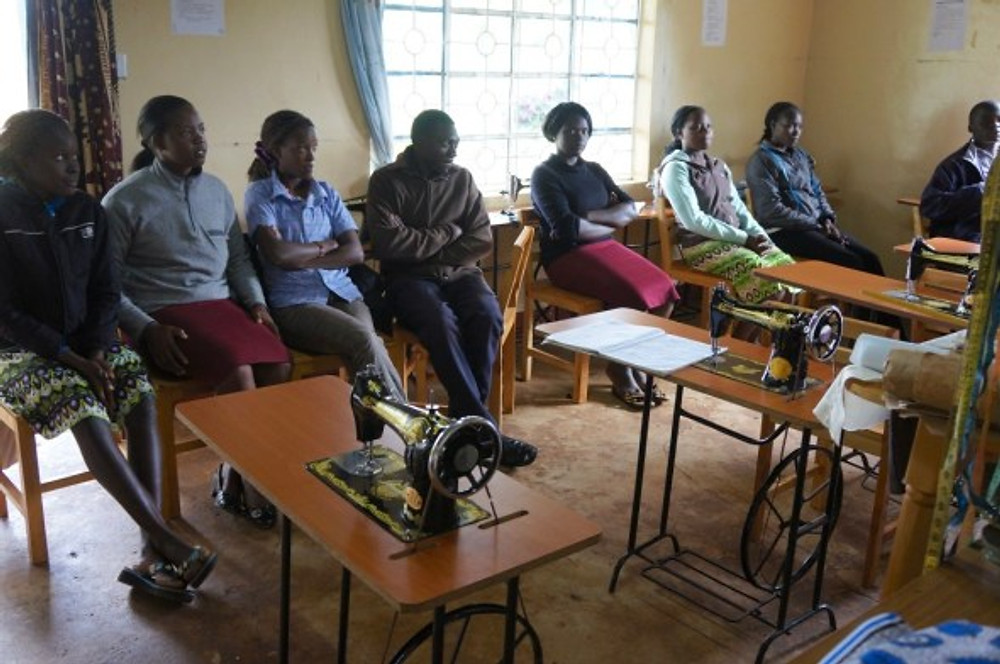 Students in the Samro Poly tailoring classroom in Eldoret, Kenya. Many are wearing clothes that they have made in the class.