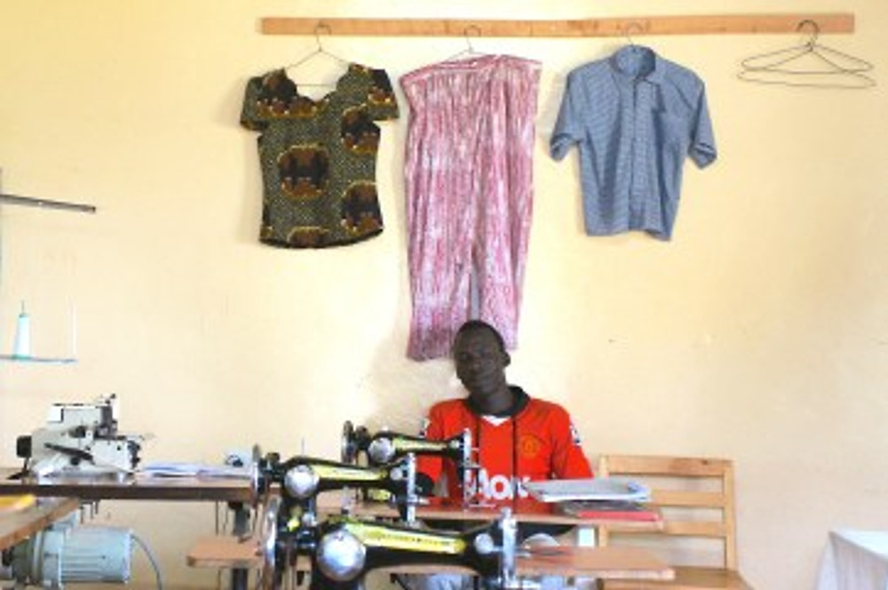 One of the Samro Polytechnic students in the tailoring classroom. With clothing made by students hanging on the wall.
