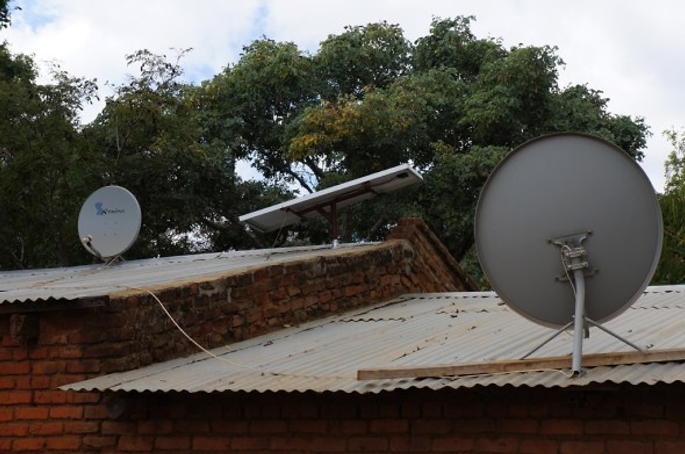 Solar panels and satellite dishes on a home in rural Malawi. #TheAfricaTheMediaNeverShowsYou