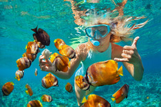 Girl diving in ocean with fishes next to