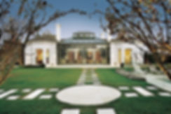 luxury white house with a green veranda and a white swimming pool