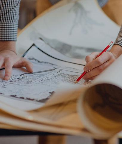 Hands designing home plan on a desk
