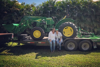 CoLab Farms owners with their new John Deere tractor.