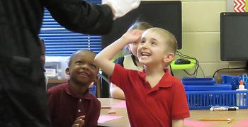 Children smiling giving a high five.
