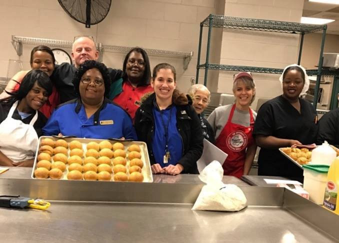 Members of our School Nutrition Department posing for a picture with some fresh rolls.