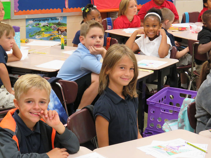 Students smiling in a classroom.