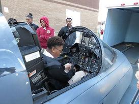 Studetns of NJROTC sitting inside an f-15 cockpit