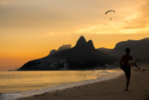 Landscape photograph of a sunset at the famous Ipanema Beach in Rio De Janeiro, Brazil with the Dois Irmaos mountain in the background