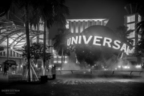 Street photograph of a black and white night street scene of the Universal sign on Sentosa Island, Singapore