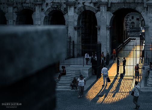 Street photograph of a sun ray beaming through one of the entrances to the ancient Colosseum in Rome, Italy
