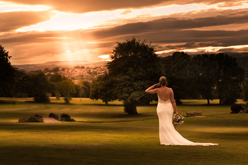 A bride posing on the Bryn Meadows golf course at sunset in Ystrad Mynach, South Wales