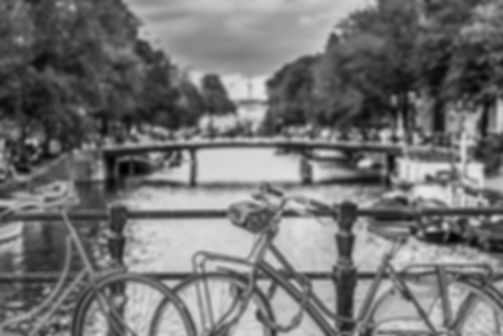 Black and white street photograph of a shot of a bicycle with the canal in the background in Amsterdam, the Netherlands