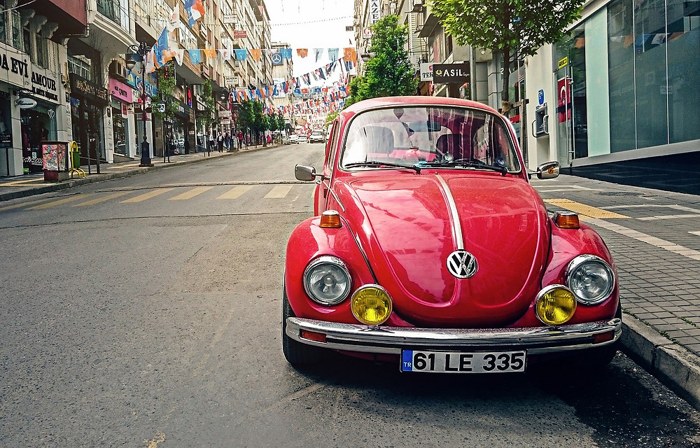 A classic red Volkswagon Beetle parked on a street